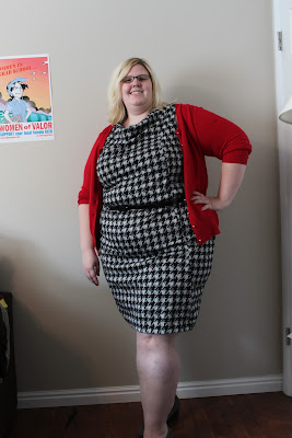 a photo of a fat pale-skinned woman wearing a black and white houndstooth dress, red cardigan and grey wedges