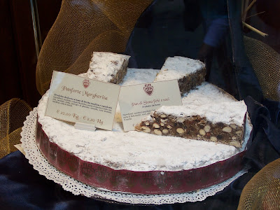 Huge rounds of panforte, studded with hazelnuts grace the windows of ...