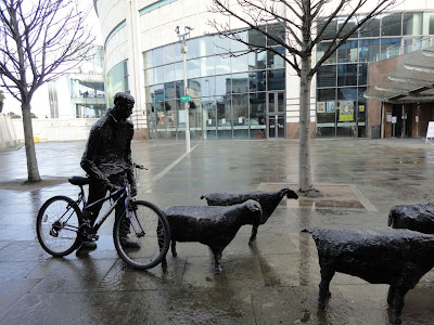 Photo of a bicycle (from someone at the NICS Live event) locked to the statue in front of the Belfast Waterfront