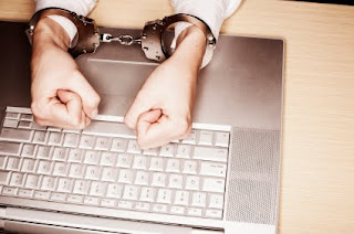 Computer user in handcuffs