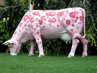 large fiberglass cow painted pink with large strawberries all over it