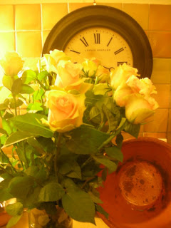 yellow roses in from of a clock