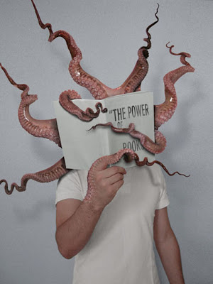 child holding up book entitled the power of books, with tentacles coming out of it.