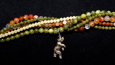 multiple strand neclace in earth tome varied beads with pewter elephant charm.