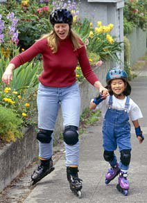 Child and her mother playing roller blade together.