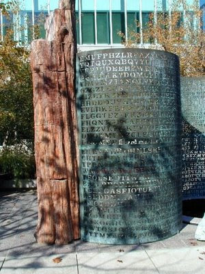 PETRIFIED WOOD: Kryptos is a 9-foot 11-inch-high main sculpture—an S-shaped wave of copper with cut-out letters, anchored by an 11-foot column of petrified wood—and huge pieces of granite abutting a low fountain