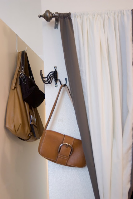The closet framed with curtains and behind the door purse storage