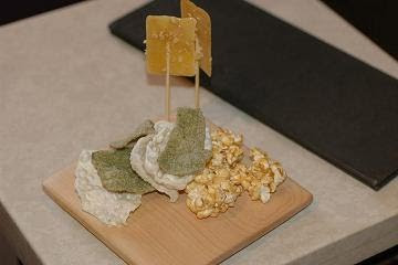 Snacks of goose fat and peanut lollipops, spiced popcorn and assorted crackers