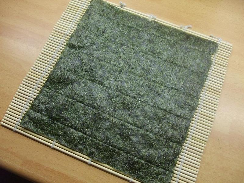 A sheet of nori laid out on a rolling mat