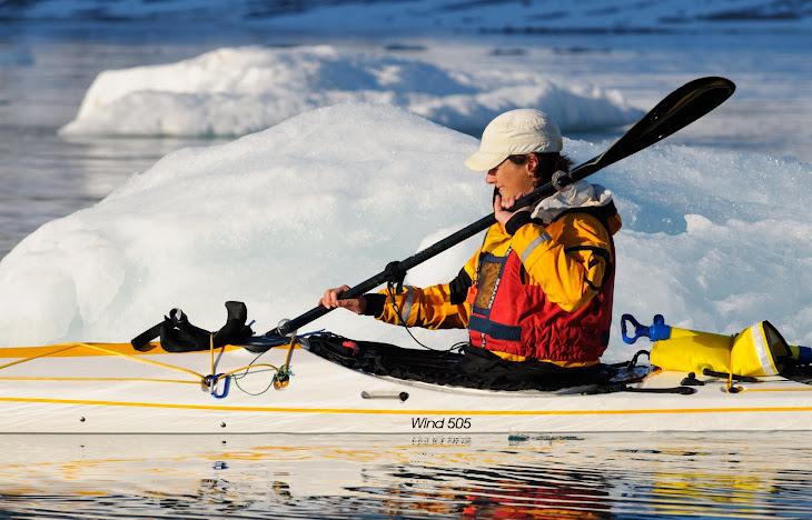 Ei glad jente padlende i Magdalenefjorden på Svalbard