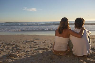 Casal na praia contemplando o mar