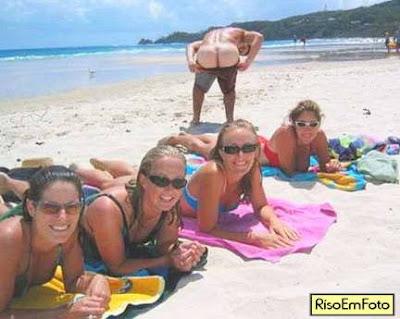 As moças fazem pose para foto na praia e o marmanjo mostra o traseiro.