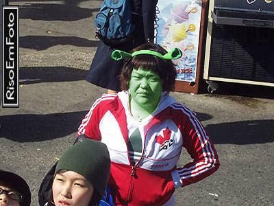 Mulher japonesa com rosto pintado de verde e orelhas de Shrek.