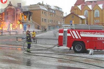 Homem do corpo de bombeiros lava o carro enquanto os outros lutam contra incêndio.
