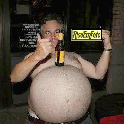 Homem gordo e barrigudo equilibra cerveja sobre o imenso abdome.