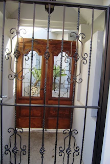 Two doors. The first, more a gate or ironwork. Beyond it, a pair of timber doors, with more iron work in the upper panels, through which is visible some cactus-y plants in pots standing in a paved courtyard. There is a space between the doors, like a portico.