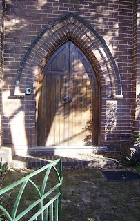 A door to a building - well, house these days. The door is timber, made of vertical slats, and shaped like an arch, but with a very pointed top. It is in two halves, and there are matching round iron rings which appear to serve as doorknobs. The brickwork surrounding the door mirrors and emphasises the pointed arch shape, as does the ironwork in the gate, visible in the front of the photo.