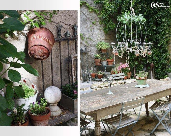 Au centre de la cour, une grande table en bois de cuisine surmontée d'un lustre en fer décoré de pampilles