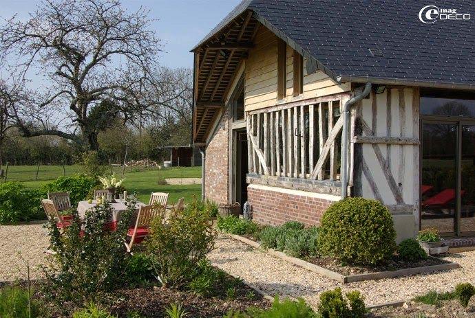 Pignon de la maison normande avec ses colombages, son soubassement en briques et sa toiture avec croupe