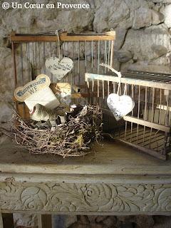 Sur une desserte fleurie, vieilles cages et nid d'oiseau