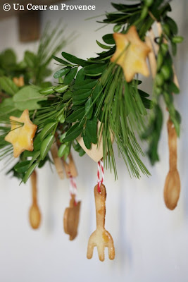 Wreath made of evergreen branches, boxwood, juniper, rosemary and decorated shortbread cookies shaped spoon, fork and star