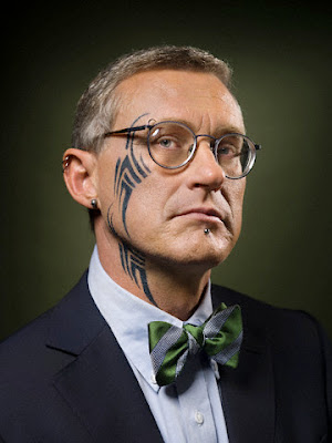 dressing in a suit with colorful bow tie has straight tribal tattoo from