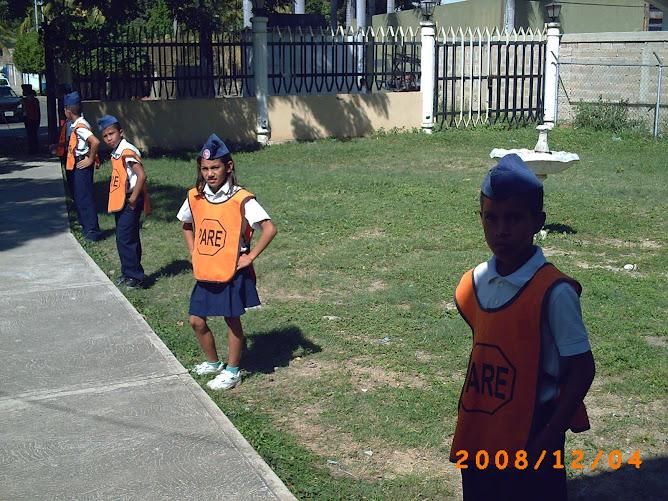 Patrulleros escolares haciendo guardia a la entrada de la iglesia.