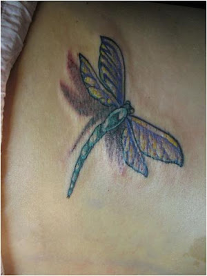 Colorful dragonfly tattoo design on the back.