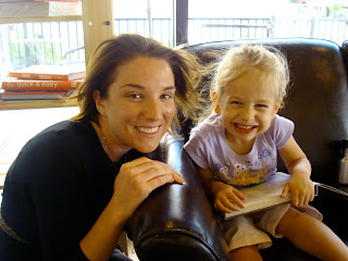 Woman kneeling next to sitting child smiling with book