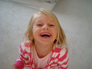 Young girl looking up at camera with big smile