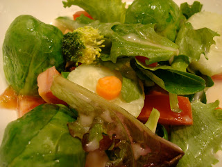 Mixed Greens with vegetables on white plate