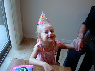 Young girl wearing birthday hat and necklace