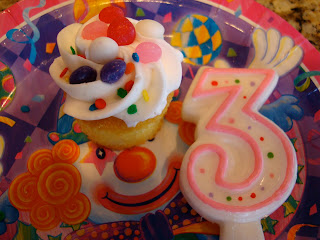Decorated cupcake on plate with a large number three candle