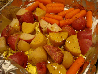 Foil lined pan of diced potatoes and carrots in olive oil and seasonings