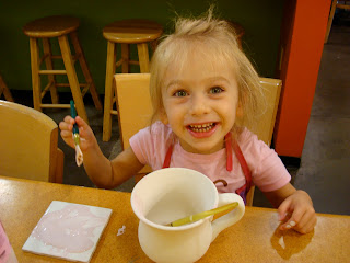 Little girl smiling while painting coffee mug