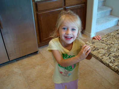 Young girl in kitchen holding onto countertop smiling