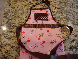 Little girls apron that is pink, brown and has cherries