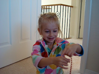 Young girl playing with red string of beads