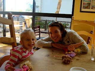 Woman and young girl at table playing with toys