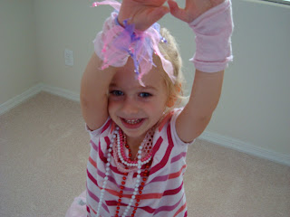 Young girl playing dress up with arms up in air