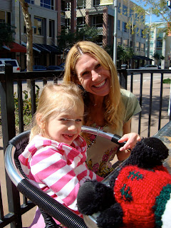 Woman kneeling beside seated child smiling outside coffee shop