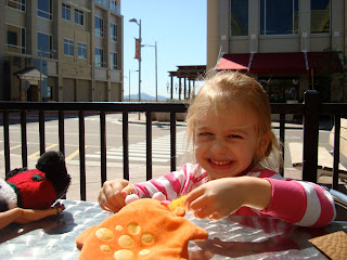 Young child sitting at outdoor table playing with toys
