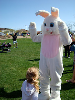 Young girl facing Easter Bunny watching him