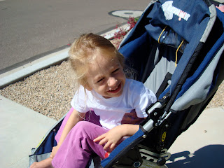 Young girl in stroller squinting with sun in her eyes