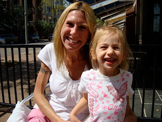 Woman and young girl smiling on outside patio