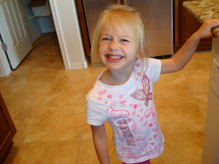 Young girl holding onto countertop smiling