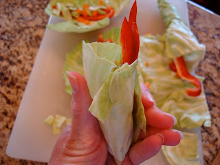 Hand holding cabbage with vegetables rolled up