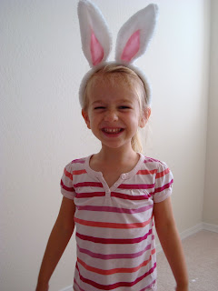 Young girl in stripped shirt wearing easter bunny ears