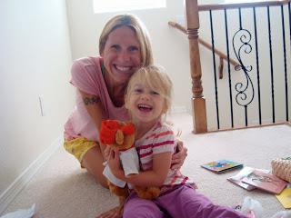 Woman and young girl hugging while holding stuffed animal