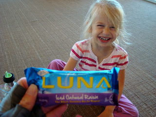 Hand holding Luna Bar with young girl smiling in background